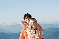 Young couple standing ,women holding binocular