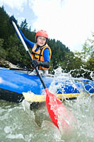 Austria, Salzburger Land, Young woman rowing kayak in lammer river