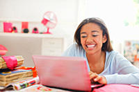 Smiling teenage girl using laptop in bedroom