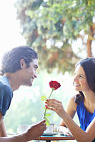 Man giving girlfriend red rose