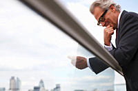 Businessman leaning on balcony railing using cell phone