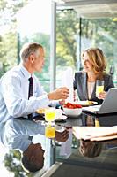 Smiling business people having breakfast