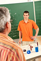 Germany, Emmering, Young man smiling with teacher in foreground (thumbnail)