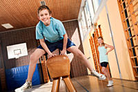 Germany, Emmering, Boy 12-13 jumping with girl standing in background (thumbnail)