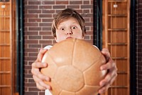 Germany, Emmering, Teenage boy 14_15 lifting ball, portrait