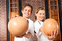 Germany, Emmering, Boy and girl 12_13 holding ball and smiling, portrait