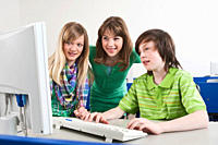 Germany, Emmering, Boy using computer and girls watching, smiling
