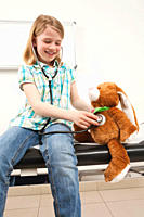 Germany, Munich, Girl 8_9 examining toy rabbit with stethoscope, smiling