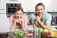 Germany, Couple with vegetables and fruits on kitchen worktop, smiling, portrait