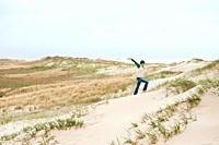 Germany, St Peter_Ording, North sea, Woman having fun on sand dunes
