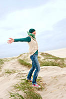Germany, St Peter_Ording, North sea, Woman standing on sand dunes