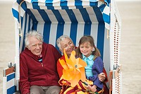 Germany, St. Peter_Ording, North Sea, Girl 6_7 sitting with grandparents on hooded beach chair