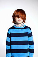 Boy in striped sweater with hair covering his eyes