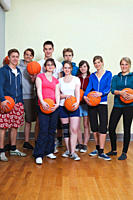 Germany, Berlin, People standing and holding basketball, portrait