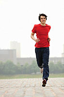 Germany, Cologne, Young man jogging, smiling