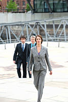 Germany, Hamburg, Businesswoman walking with business people in background