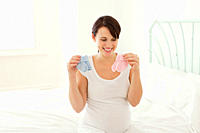 Pregnant woman looking at blue and pink baby socks