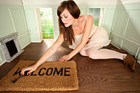Young woman in small room with key and welcome mat