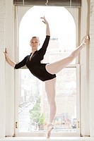 Ballerina poised in window