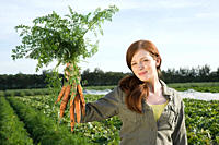 Young woman holding bunch of carrots in field