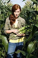 Young woman holding corn cob