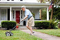Senior man mowing his front lawn