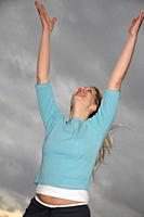 Woman stretching out arms in front of dark clouds, low angle view