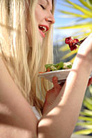 Young blond woman eating salad, smiling