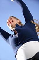 Young woman jumping happily in front of blue sky, view from below