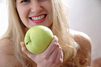 Young blond woman holding green apple, close up