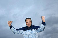 Young man in a sweat suit jacket cheering in front of dark clouds