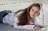 Germany, Bavaria, Teenage girl lying on sand dune, portrait