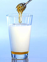 Honey dipper with glass of milk, close_up
