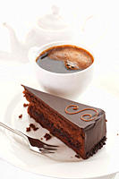 Slice of Sacher cake in plate with coffee cup and kettle in background