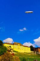 A zeppelin flies above the medieval city of Meersburg on Lake Constance Bodensee, with vineyards below, Baden-W&#252;rttemberg, Germany
