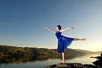 A young woman practises her dance over Kamloops lake at sunset, Kamloops, British Columbia, Canada