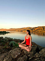 A young women practises the art of Yoga on a beautiful evening over Kamloops lake, Kamloops, British Columbia, Canada
