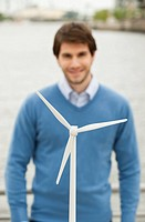 Germany, Hamburg, Close up of wind turbine, Businessman smiling in background