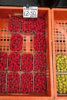 Punnets of local raspberrys for sale outside a greengrocers shop store in the Uk