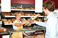 A sales clerk helping a customer at a bakery