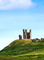 Dunstanburgh castle ruins on a hill hilltop on the North East coast of England