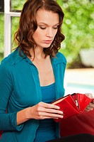 Young woman opening purse