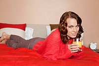Young woman drinking orange juice in bed