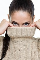 Young woman covering her face with sweater