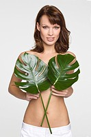 Young woman covering breast with leaves