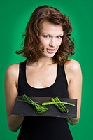 Young woman holding tray of asparagus and chives