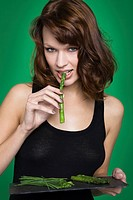 Young woman eating asparagus
