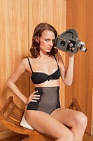 Young woman in underwear using old_fashioned movie camera
