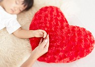 Hands of parent and child on the heart shaped cushion