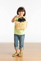 A Girl Holding A Basket With A Rabbit In It